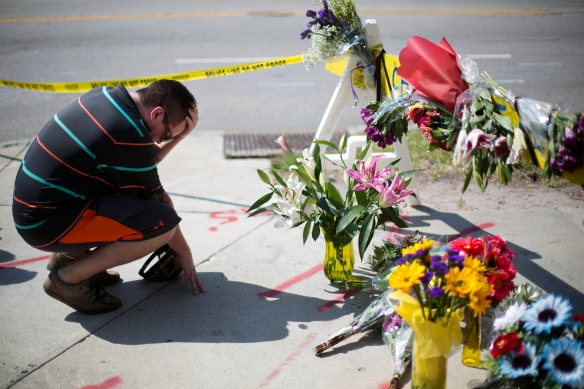 Noah Nicolaisen, of Charleston, S.C., kneels at a makeshift memorial, Thursday, June 18, 2015, down the street from where a man opened fire Wednesday night during a prayer meeting inside the Emanuel AME Church, killing several people in what authorities are calling a hate crime. (AP Photo/David Goldman)