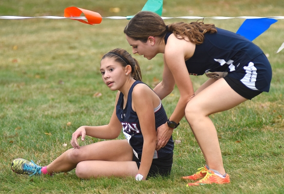 New Fairfield's Kristen Richichi, right, stops to help a fallen Sarah Leavens of Avon during Saturday's Connecticut State Open championship meet.